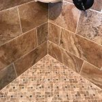 Photo of shower wall and floor using two different tile styles.