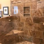 Photo of glass and earthtone tile shower installed by Arnold Flooring.